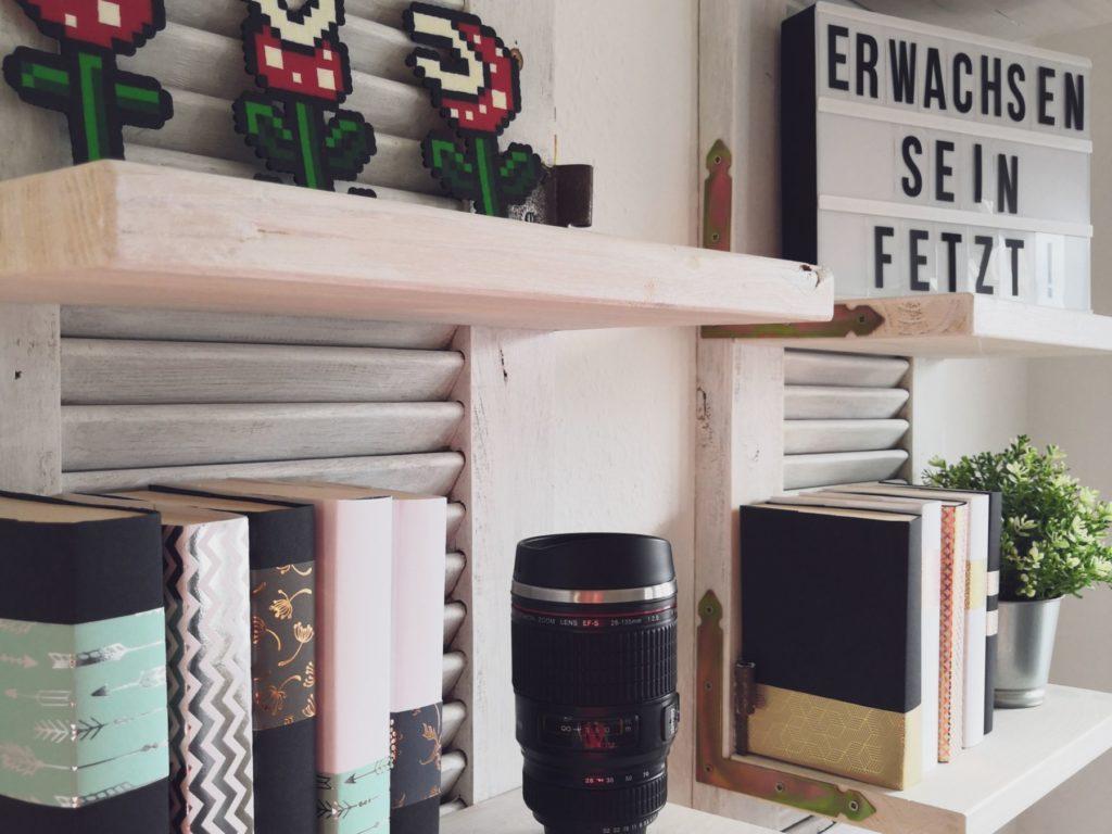 Projekt-Teaser mit Klappladen-Regal und Bucheinbänden (erster Blogbeitrag)